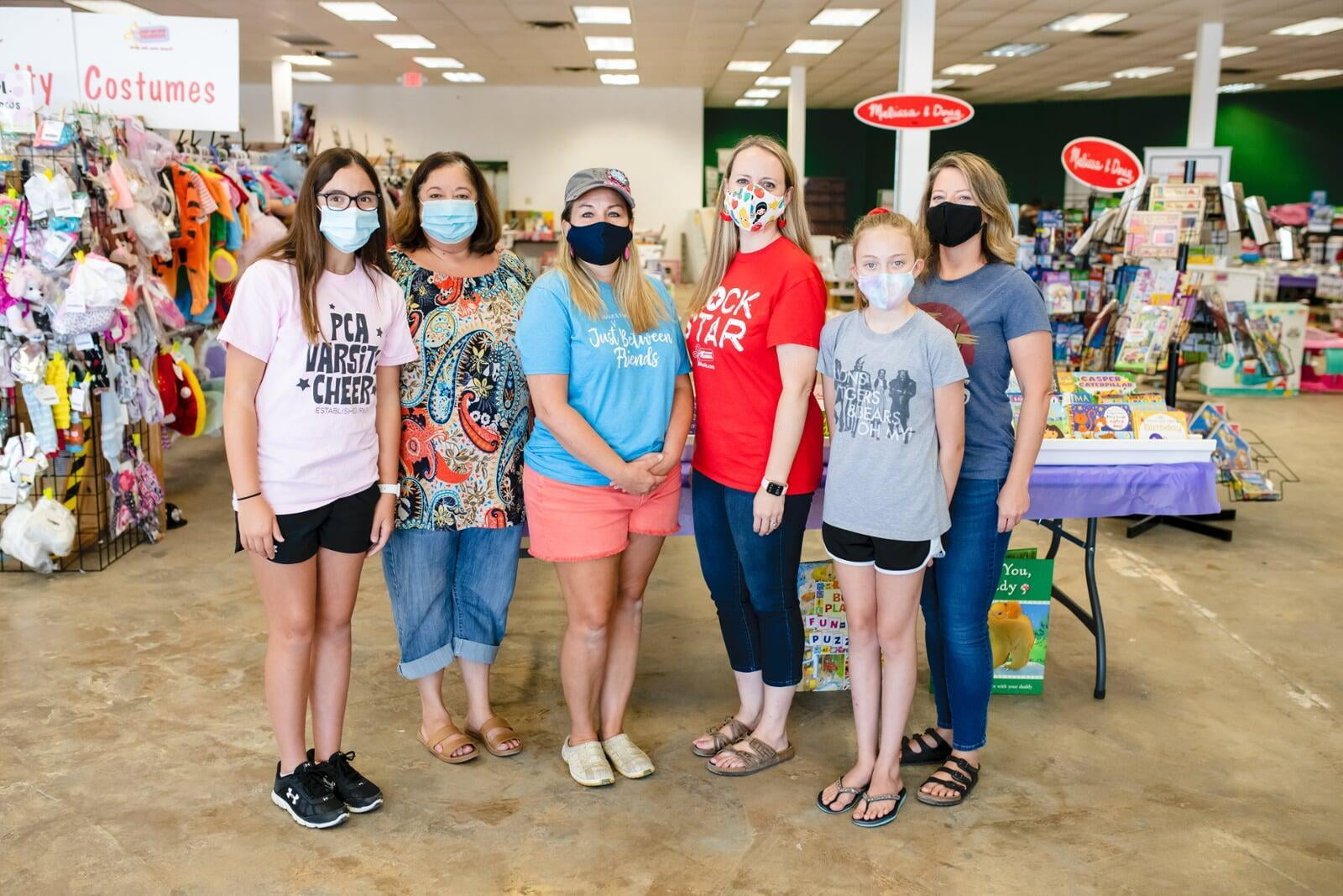 A group of shoppers wearing masks for safety reasons gathers together at the sale to shop.